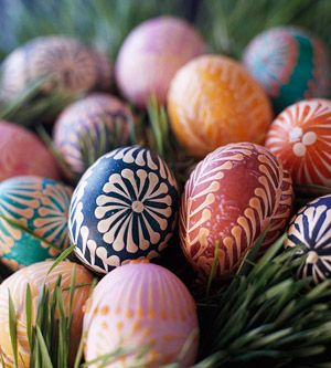 These eggs were decorated using Pysanky, the ancient Ukrainian folk art of wax-and-dye egg decorating. To create these designs, stick metal pins in pencil erasers, dip the pinheads in melted wax, and draw wax patterns on hard-boiled eggs before dyeing them.
