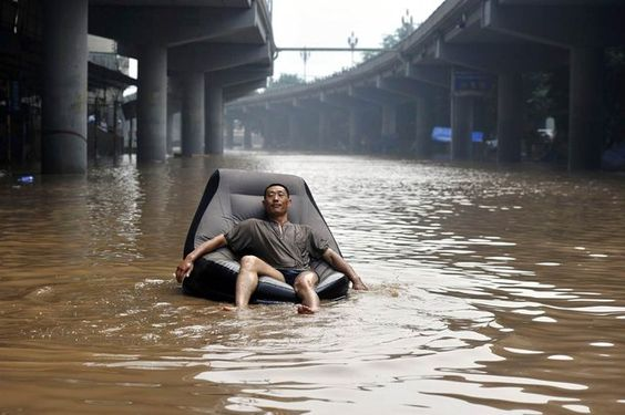 A man sits on an inflatable sofa floating on a flooded street near the Yangtze River in Chongqing, China, July 25, 2012. Torrential rain that battered 17 provinces since July 20 has left 95 dead and another 45 missing. (Photo by Shi Tou/Reuters)