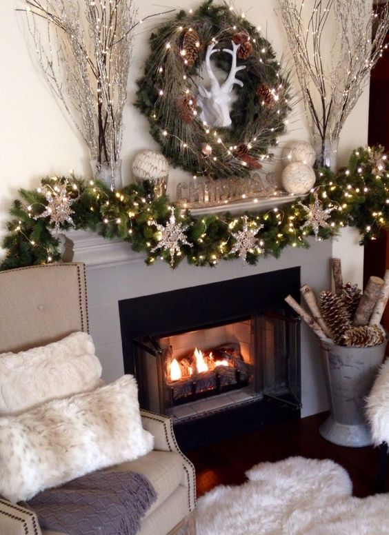 snowflake ornaments covered in silver glitter, and tiny glowing string lights, on a green garland, made from faux pine branches, decorating a grey and black fireplace, in a cozy living room, fireplace decor ideas!