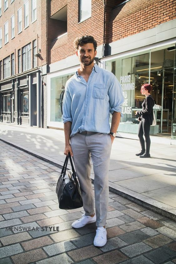 Freddie on the streets of London in 2019 wears Denim Shirt, Grey Trousers, White Trainers, and Black Leather Gym Bag.