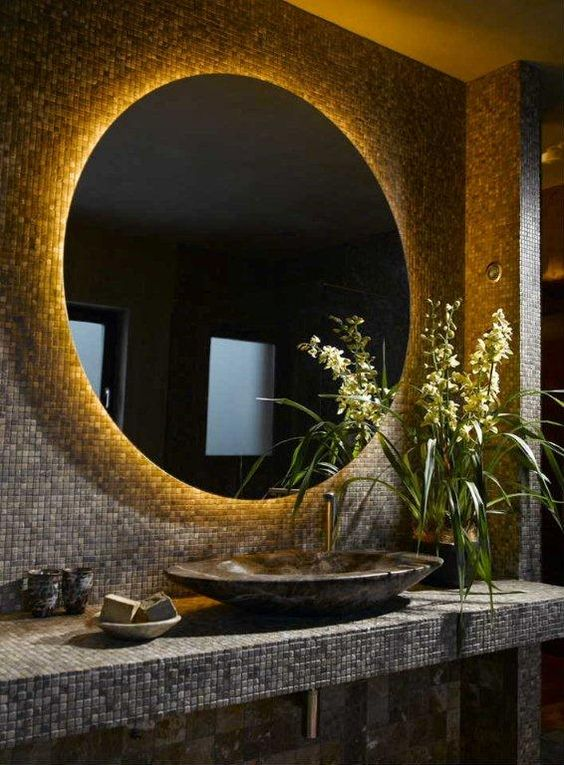 Ultra dark bathroom interior with LED retrofitted oval mirror. Ultra warm white…