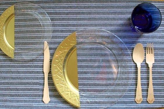 Materiais:    Pratos de plástico  Spray dourado  Fita adesiva  Máscara  Luvas  Passo a passo:Marque o prato com a fita adesiva, delimitando a parte que será pintada. Nós escolhemos pratos transparentes com a tinta dourada, mas você poderá fazer com a cor que preferir.Depois que você marcar todos os pratos, passe a tinta em spray na área que deseja pintar.IMPORTANTE: Não passe a tinta em spray do lado do prato onde as pessoas irão comer! O trabalho deverá ser feito na parte de trás. Espere…