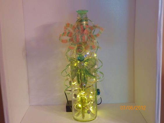 Dragonfly bottle, $35.00, Acrylic painted dragonfly on front of bottle, green diamond stopper, fuzzy bright colored ribbon, orange custom made jewelry hanger, on back see dragonfly jewelry (gold) and gold ladybug charms on front & back with painted ladybug gems on front/back of bottle, gold LED lights with 3 way timer.