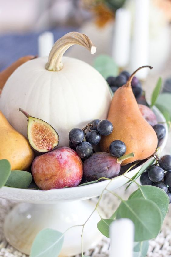 A beautiful tablescape with rich fall colors featuring a centerpiece of fall fruits: Plums, pears, figs, and grapes surround a simple white pumpkin. #fallharvest #harvest #healthyfood #fall #fallvegetablegardening #fruit #vegetables #healthylivingtips