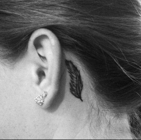 behind the ear. feather tattoo. simple.