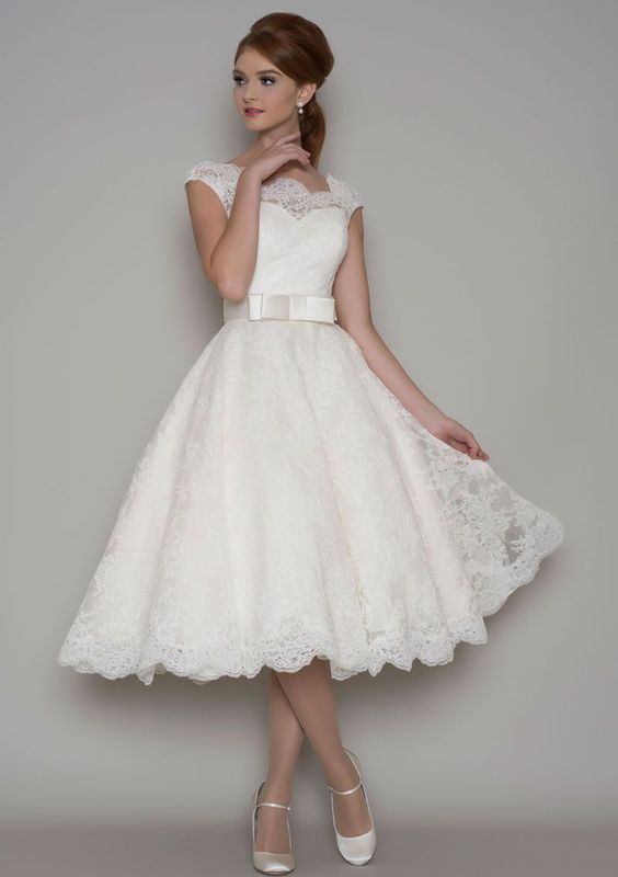 This vintage tea length a-line wedding dress features strapless sweetheart underskirt skirt with illusion sheer lace overlay. Cap sleeves, matching with sash.