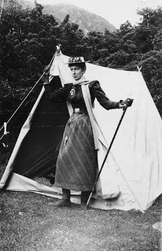 May Kinsey in climbing dress standing outside her tent.:
