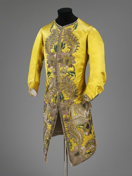 Waistcoat, England, 1730-1739. Yellow silk satin, richly-embroidered with large stylised exotic flowers and leves with feathered srolls in coloured silk an metal threads of several textures, arranged in broad borders down each front, over the pocket flaps and the front of the waistcoat skirts. This waistcoat is unusually opulent as the expensive satin has been used not only for the front of the garment but also for the back and the three-quarter length sleeves.