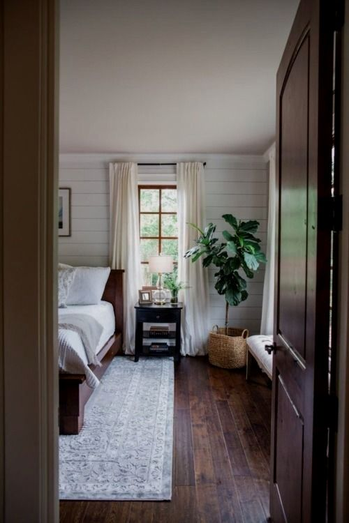 Minimalist Neutral Bedroom With Dark Wood Floors A Potted Tree Wood Bed Frame Gray And White B Gray Master Bedroom Remodel Bedroom Home Decor Bedroom