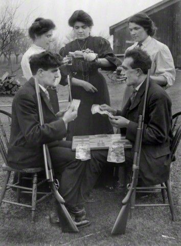 HUMOR: Group of adults partake in many vices. Three women and two men gamble, drink alcohol, smoke cigars, and have weapons ready for gun play in a staged photograph  from 1910.