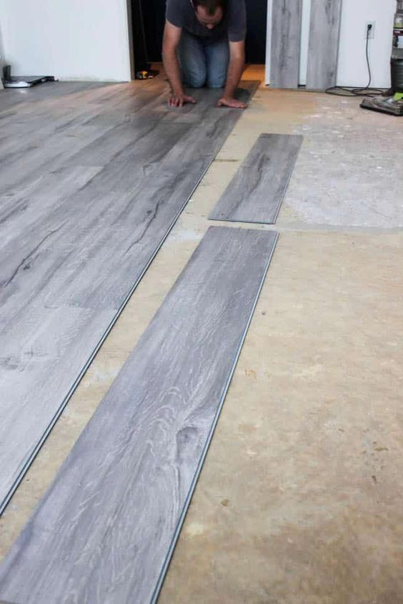 An easy step-by-step guide to installing vinyl plank flooring! A great video tutorial for learning to install new flooring and transform any bedroom, basement, kitchen, etc. Love this light grey vinyl plank flooring! #basementfloor
