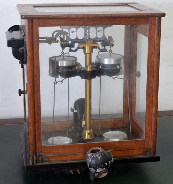 Balança de precisão em metal amarelo e branco, caixa de madeira com proteção de vidro branco transpa