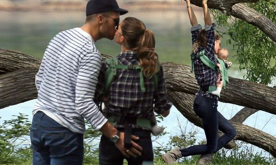 Cheeky monkey! Gisele Bundchen steals a kiss and pat on the bottom from Tom…