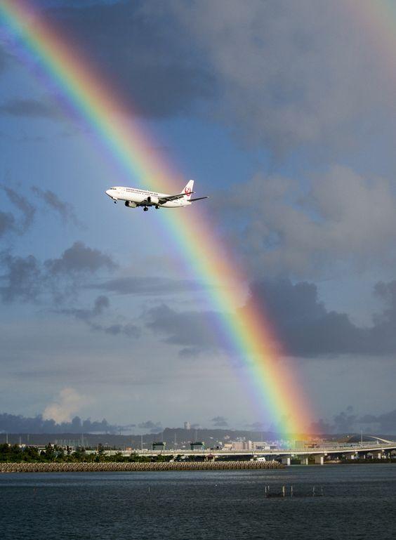 虹の前を飛ぶ飛行機