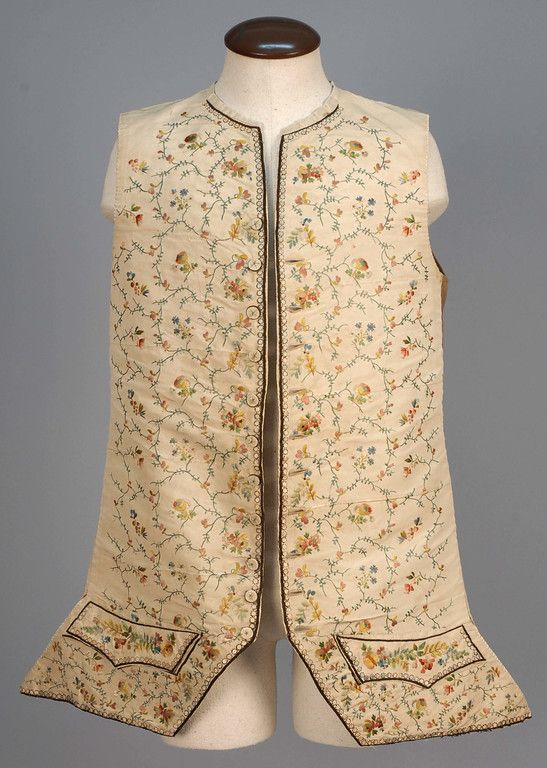 Waistcoat, c. 1770. Ivory faille having allover polychrome embroidered flowers and vines, embroidered buttons, shaped pocket flaps and hems trimmed with silk covered sequins, brown linen back with waist adjustment and linen lining.