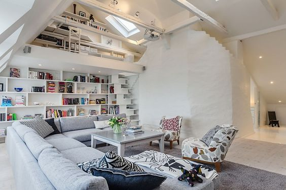 Found on Skeppsolmen, this 1,517 square foot attic penthouse with a double-height living area is located in Vasastan, a city district in central Stockholm, Sweden.