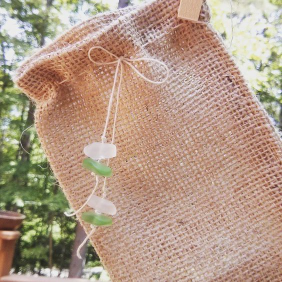 Re-stringing inexpensive burlap bags with twine and finishing with sea glass beads makes them special.