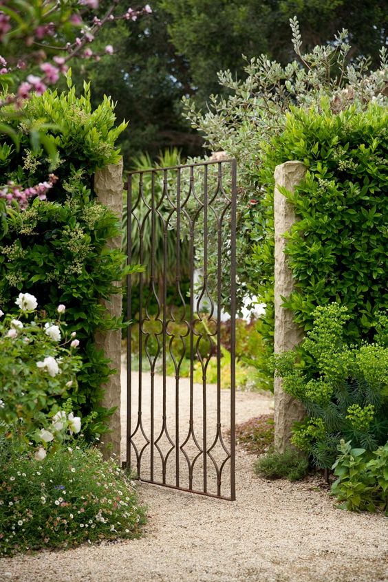 Garden gate ideas and garden inspiration: a beautiful iron garden gate at teh entrance to a lush blooming garden. #gardengate #FrenchCountry #gardenideas #Provence #courtyard