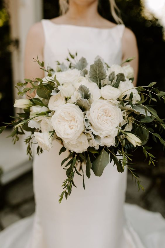 This navy and peach wedding, with cream roses EVERYWHERE, had just the right touches of Southern wedding charm and classy details. The bride carried a luxe bridal bouquet made of enchanting greenery and lovely white roses.