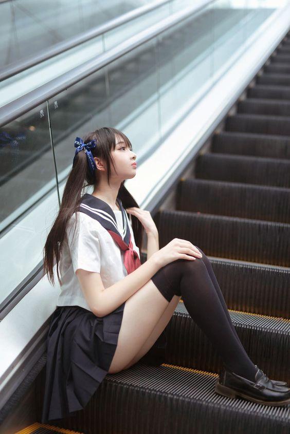 水手服美少女坐在手扶梯的階梯上