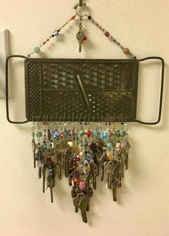Vintage cheese grater with keys, buttons, beads and electronic resistors.