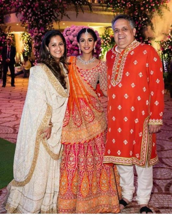 Radhika Merchant in a red orange Abu Jani Sandeep Khosla lehenga for Ambani Wedding. #Frugal2Fab