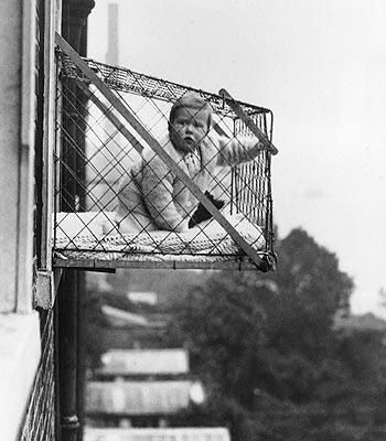 East Poplar. A 'Baby Cage' given to residents for their tenement windows.