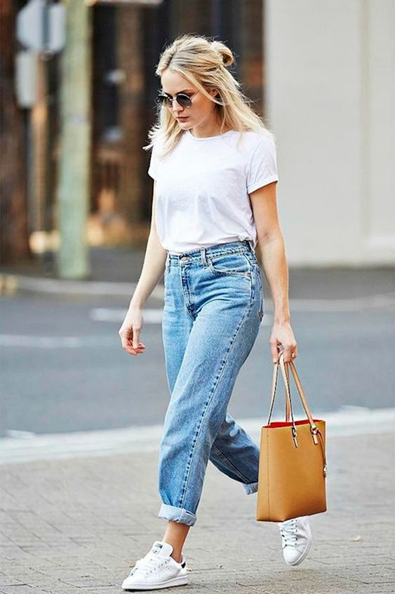 Look básico e cool com óculos redondo, camiseta branca, mom jeans claro, tênis stan smith branco e bolsa bege: