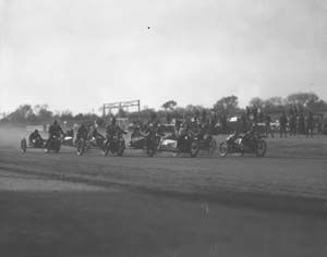 Motorcycles racing down the track at the Kern County Fair Association Race Track, 11-30-1930