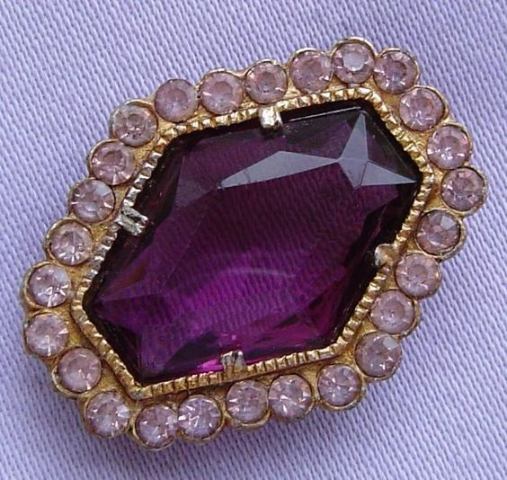 This lovely brooch is adorned with a gorgeous large amethyst glass stone surrounded by little shimmering pink faceted glass rhinestones. The large stone is faceted on both faces and mounted in an open-back claw setting.