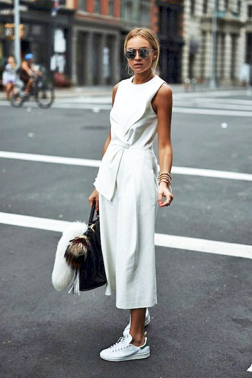 Blogger Nina Suess is spring-ready in a chic statement tie-front culotte jumpsuit, mirrored Dior shades and Adidas Stan Smith sneakers. We can't help but love how her embroidered oversized Fendi bag spices up the otherwise monochrome look. One of our favorite perks about wearing a jumpsuit is that it can easily take you from day to night.: