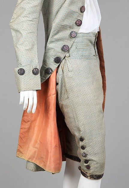 Suit, French, 1765-75. The distinctive buttons on this 18th-century suit characterize the flamboyance with which French men dressed to match the opulence of their female counterparts. The liberally applied buttons would have been a lively pink color and glittering in candlelight next to the elegant textile and salmon-colored lining.