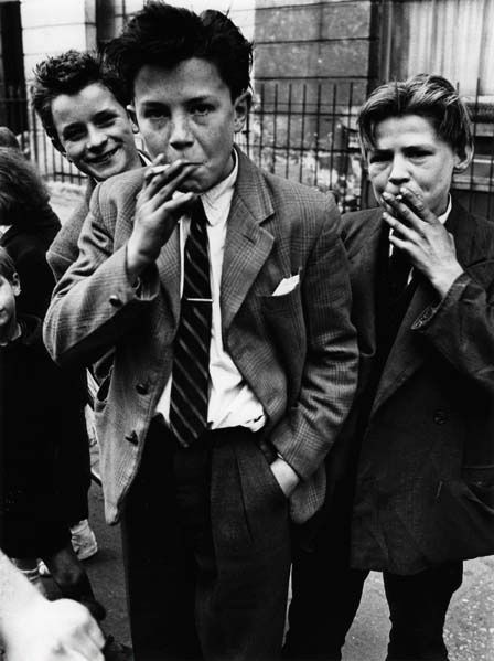 Roger Mayne photographed these young boys in North Kensington. Wearing oversized draped jackets and quiffed hair, they emulate the Teddy Boy fashion of the 1950's. Breaking from convention, teenage youths embraced the casual and affordable American-influenced style and culture.