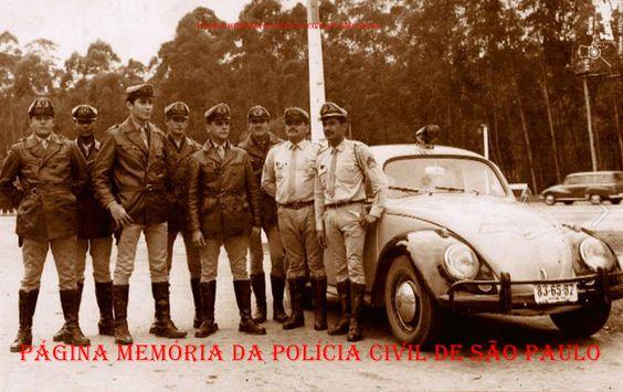 """Integrantes da extinta Polícia Rodoviária do Estado de São Paulo ao lado de uma viatura marca VW- Sedan """"Fusca"""", na década de 60."""
