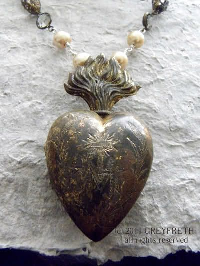 "The antique Ex Voto of the Sacred Heart was found in France. Beautifully engraved on the front is a graceful letter ""M"" for ""Marie"", a cross, and sinuous foliage. The piece is quite old and time and the elements have left their mark by way of a stunning patina in variegated hues. It appears almost as though this piece was buried deep in the earth with its secrets, and then rediscovered."