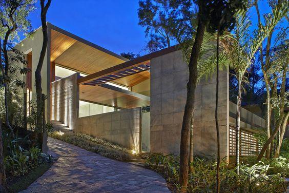 Com fachada discreta e camuflada em meio à vegetação, a casa projetada em um condomínio na cidade de Nova Lima, Minas Gerais, concentra seus encantos na fachada dos fundos, onde living e área de lazer integrados desfrutam da vista da mata atlântica