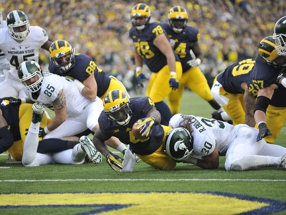Michigan running back De'Veon Smith is stopped just