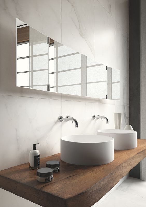 """Marble bathroom with recycled timber vanity and white basin. Calacatta marble is formed through a metamorphic process which causes a complete recrystallization of calcium carbonate. The low refractive index of calcite allows light to """"penetrate"""" the surface of the stone before being reflected, giving it a special brightness."""