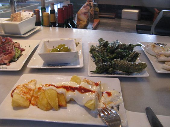 Patatas bravas, pimientos de padron y aceitunas at my favourite tapas bar in barcelona. cuines de santa catarina
