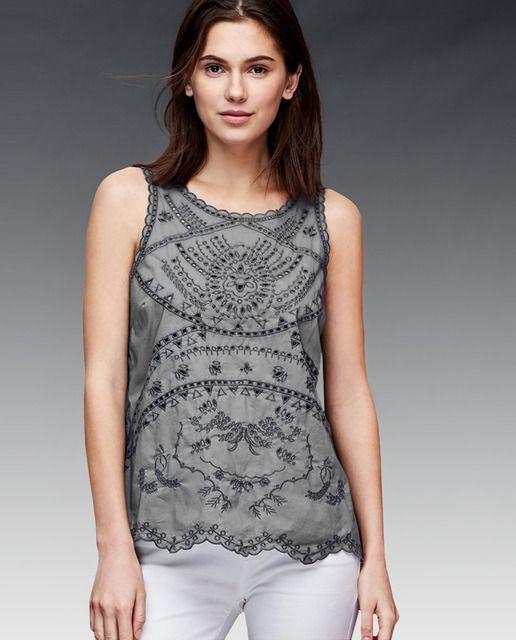 Top en color gris con trabajo bordado. Sin mangas, con cuello caja y lazo en la espalda.