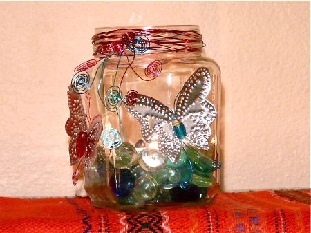 mason jar luminaria with: punched tin butterflies, colored wire, glass globs.