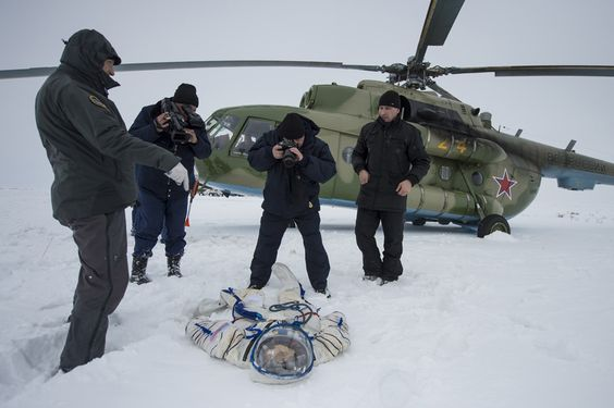 A photographer and an operator document the suit worn byAstronaut Michael Hopkins from NASA after the landing of the Soyuz TMA-10M capsule in a remote area southeast of the town of Zhezkazgan in central Kazakhstan, March 11, 2014. REUTERS/Bill Ingalls/NASA