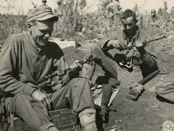 WWII soldiers in central Burma cleaning, oiling, and loading their rifles.  Photographer Unknown.