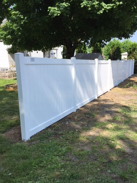Beautiful White Solid Vinyl Privacy Fence Separates This Property