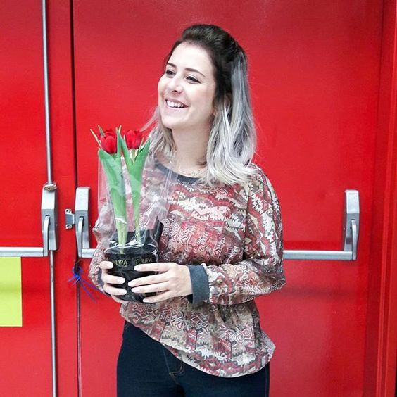 Foto menina loira cabelo platinado com blusa de estampa étnica segurando um vaso de tulipas em frente a uma porta vermelha