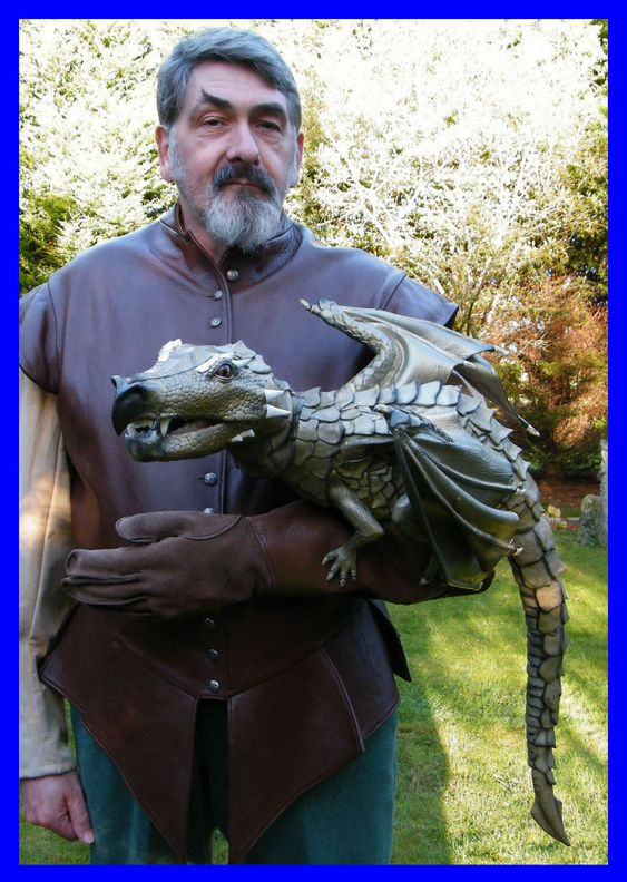 """Dragon puppet - His hand is in the dragon and his """"arm"""" is stuffed."""
