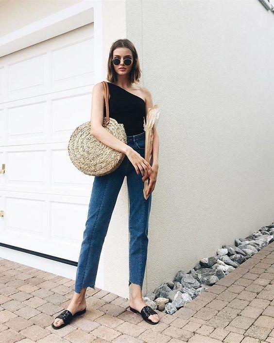 Um ombro só: 11 Looks que vão te convencer a embarcar na trend. Blusa preta, calça jeans cropped, slide preto, bolsa de palha maxi redonda