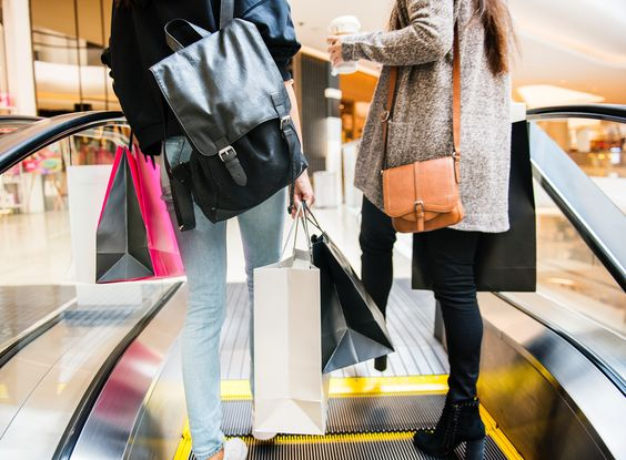 two women with shopping bags in mall