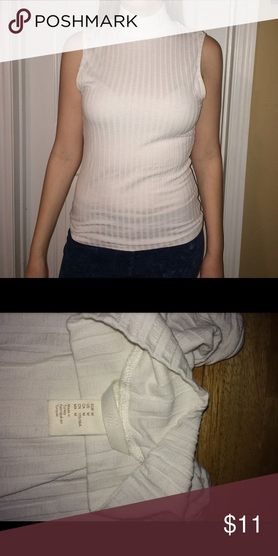 White ribbed sleeveless blouse with a turtleneck! The material is a tiny bit see through but nothing unwearable, and the fabric is so soft and silky! There is a little discoloration in the arm area but nothing noticeable! Great top for any outfit :) H&M Tops Tank Tops