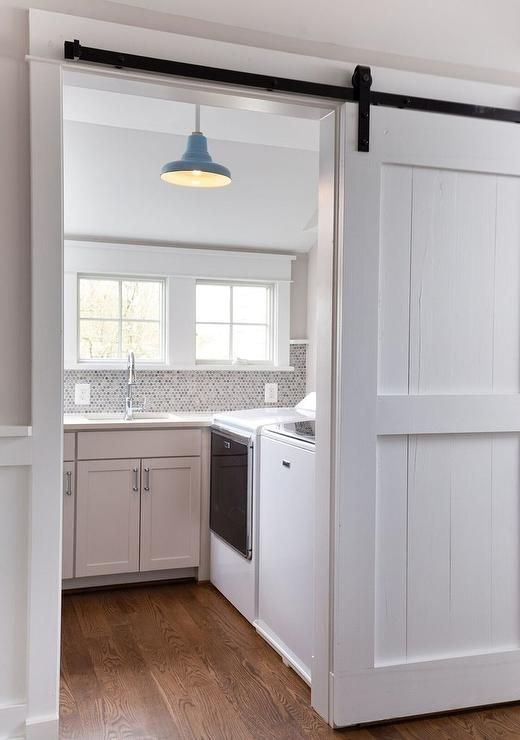 White Cottage Laundry Room Enclosed With A Sliding White Wood Barn Door On Black Rails Kitchen Barn Doors Wood Barn Door White Barn Door